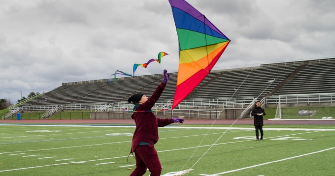 Students from Coalesce flying a rainbow kite on the football field.