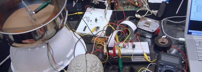 Protoboard and wiring connecting circuits to a model of a brain.