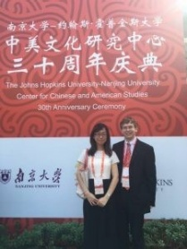 UB graduate Daniel Loebell posing in front of of the John Hopkins University-Nanjing University Center for Chinese and American Studies 10th Anniversary Ceremony poster.