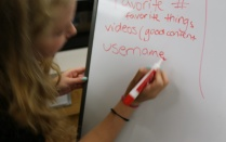 Graduate student using a white board to describe internet safety.