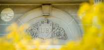 UB logo in front of yellow flowers.