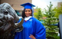 Student in graduation gown with Buffalo statue.