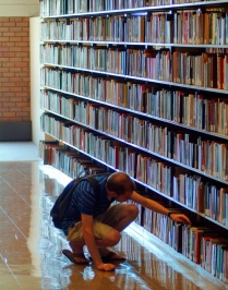 Student browsing library shelves.