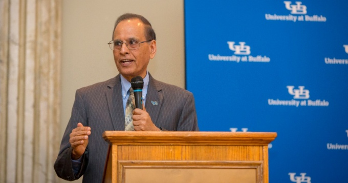 University President Satish Tripathi speaking at a podium.