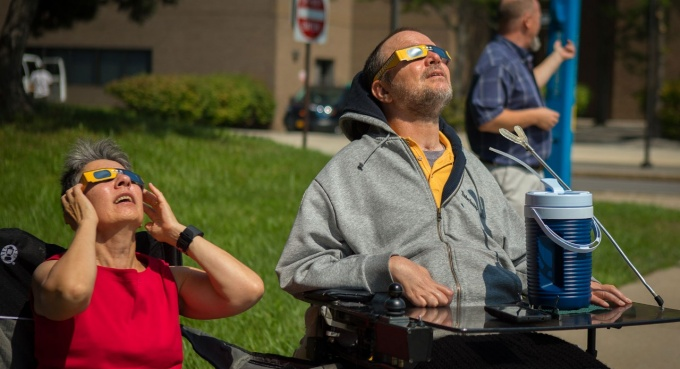 Two people observing a solar eclipse.
