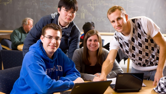 Undergraduate students gathered around a computer.
