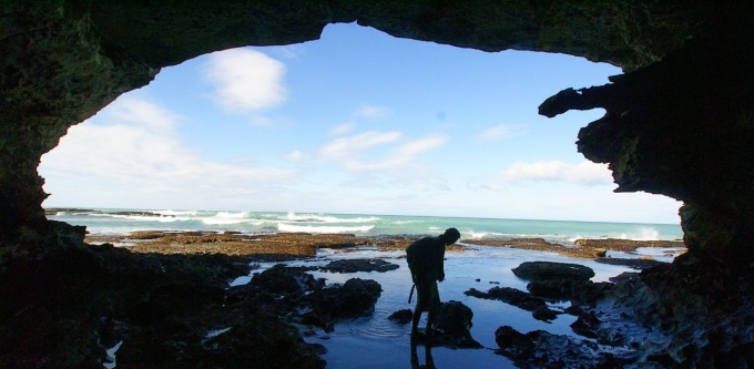 Student in oceanside cave.