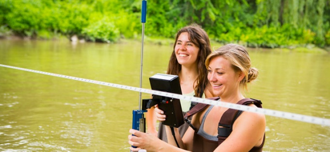 Two geology graduate students study river water.