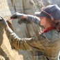 MA Student Kayla Hollister removes sediments from a wall near Fairbanks, Alaska.