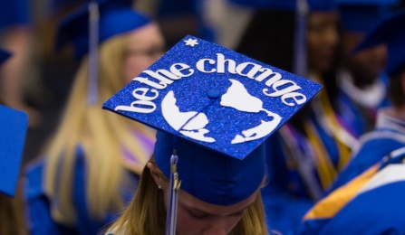 "UB student at graduation with decorated mortar board that reads ""be the change""."