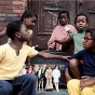 African American children with dolls sitting on a stoop.
