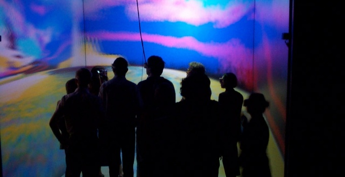 students in silhouette in front of colorful wall projection.