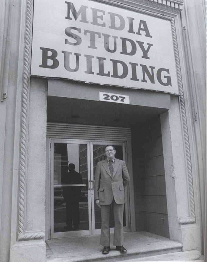 Gerry O'Grady in front of Media Study Buffalo sign in downtown Buffalo.