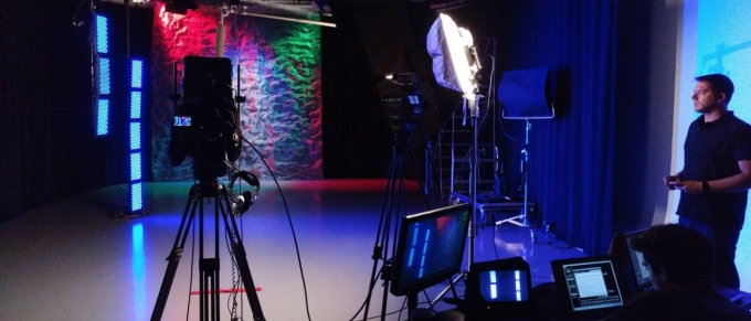 Students in studio with lighting and photo equipment.