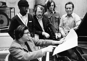 An archival photograph of Morton Feldman, seated at piano, surrounded by Creative Associates including composer David Del Tredici, percussionist Jan Williams and composers Julius Eastman and William Appleby. Photo: UB Libraries.