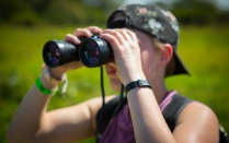 Student holding binoculars on a study abroad trip in Costa Rica.