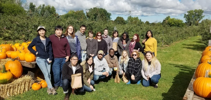 Group of students and professors on a pumpkin farm.