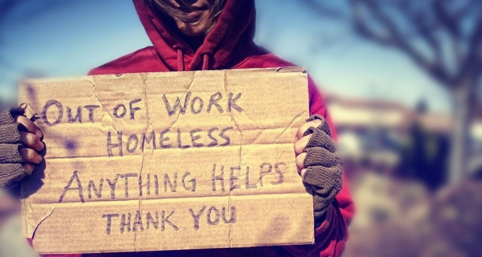 Person holding cardboard sign asking for help due to homelessness.