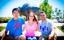 Three students sitting in front of the Buffalo statue.