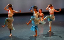 three dancers in blue dresses with fedoras.