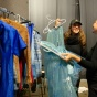Students backstage with costume rack.