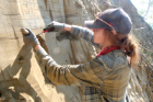 Kayla Hollister, UB geology master's student, carefully removes a section of sediment from the wall of a mine. Credit: Elizabeth Thomas