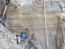 A shovel, tape measure and other tools are perched against the deposits of loess and ancient soil that form the wall of a mine. Layers of volcanic ash, also found in the wall, can help scientists determine the age of different sections of sediments. Credit: Elizabeth Thomas