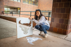 Rachel Lim uses chalk and a stencil to fashion the Bulls' spirit mark during Spirit Week activities. Photo: Douglas Levere