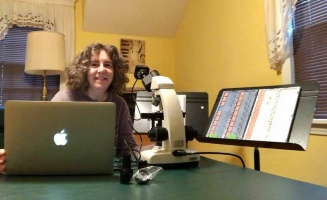 Professor Gail Seigel in her home lab with microscope and music stand for slides.