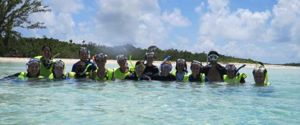 Students scuba diving at coral reef.