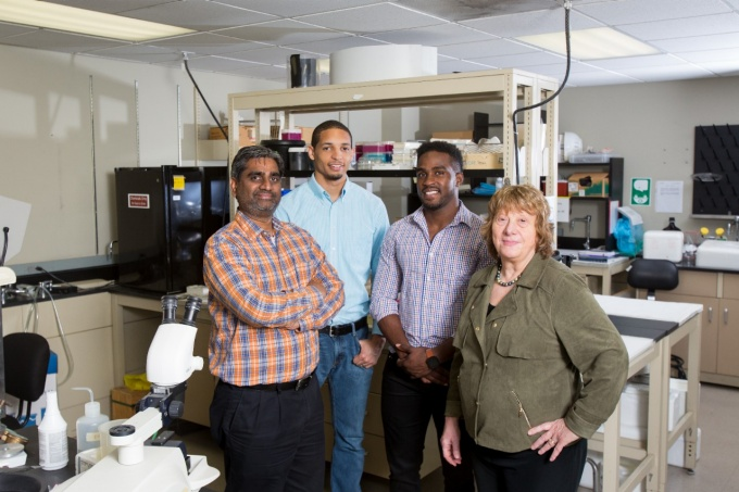 Portrait of IMSD Grant group including Rajendram Rajnarayanan (left), Anthony Jones, Kerri Pryce, and Margarita L. Dubocovich, (right) of Pharmacology and Toxicology, in a lab in Farber Hall.