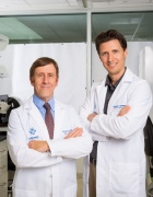 Bruce Troen, left, and Ken Seldeen, in white coats in lab.