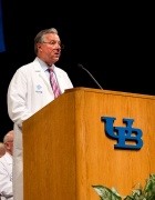 Michael Cain, MD, in white coat at podium.