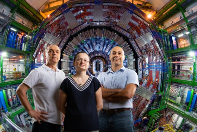 Three people standing in front of a colorful mechanical device.