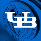 White interlocking UB logo with a school emblem in blue as the background.