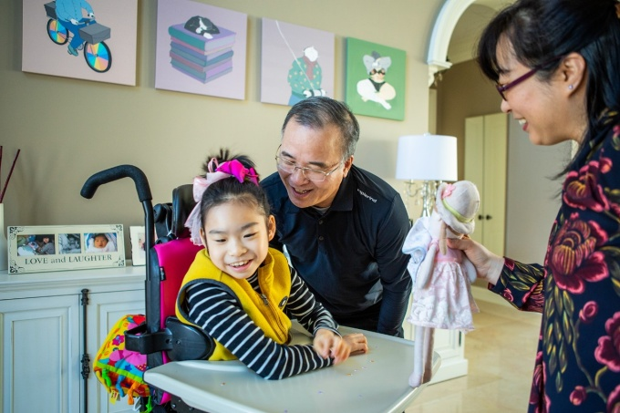 Yuna Lee gives a big smile as her father and mother play with her at home.