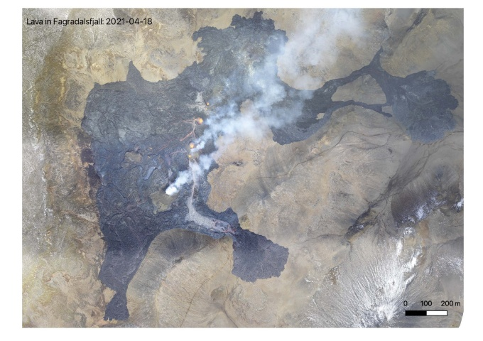 An aerial view shows a dark lava field on the landscape, with smoke coming off of it.