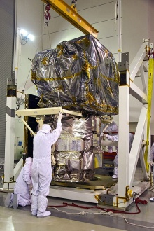 Technicians assist as a crane rotates NASA's Ice, Cloud and land Elevation Satellite-2 (ICESat-2) into position for removal and lift to a work stand in the high bay of the Astrotech Space Operations facility on June 14, 2018, at Vandenberg Air Force Base in California.