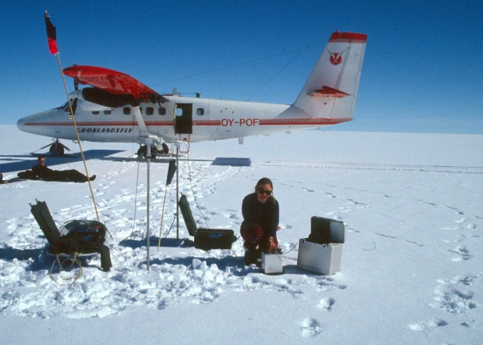 Beata Csatho makes gravity measurements on the Greenland Ice Sheet. A small plane is in the background.