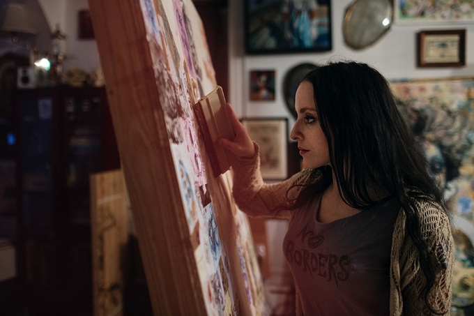 sideview of Molly Crabapple working on a painting.