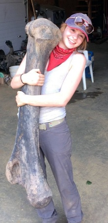 A scientist hugging a mammoth bone almost as tall as she is.