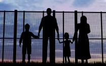 Silhouette of a family standing in front of a border fence.